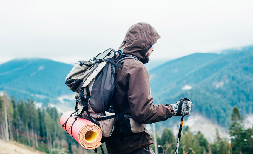 Hiker with trekking poles in polyester jacket